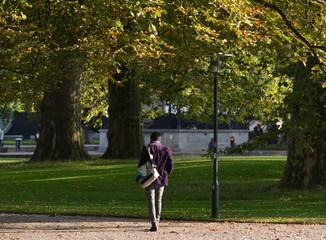 homme seul marchant dans un jardin public