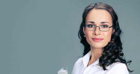 Businesswoman in glasses, on gray