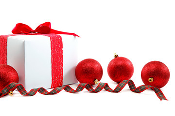 White gift box with red ribbon and christmas balls around.