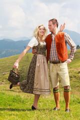 Bayerisches Liebespaar in modischer Lederhose und Dirndl
