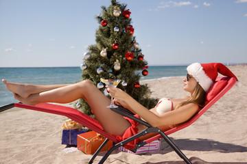 girl in a Santa hat celebrating Christmas on beach