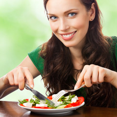 Portrait of happy smiling woman eating salad on plate, outdoor
