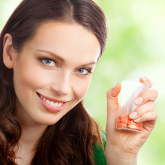 Woman showing bottle with pills, outdoor