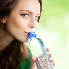 Woman drinking water from bottle, outdoor