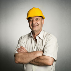 Happy mature architect in helmet standing with crossed arms
