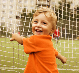 portrait of little cute boy on football field