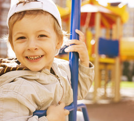 little cute boy on swing outside, playground background