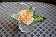 Glass vase with a single orange flower.