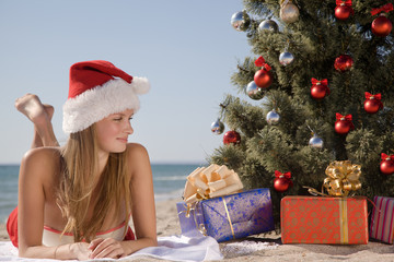 young girl in the beach resort lying under the Christmas tree