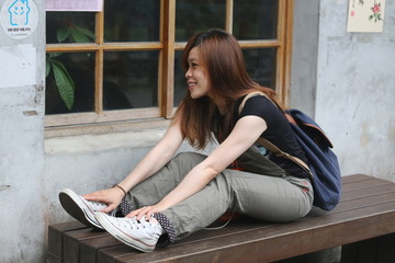 Woman of Asian sitting bench