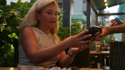 Woman paying for cafe by credit card reader