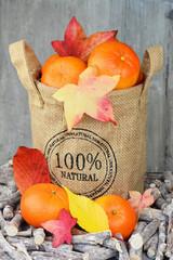 Jute zak met mandarijnen en herfstbladeren