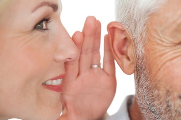 Woman whispering secret into a mans ear