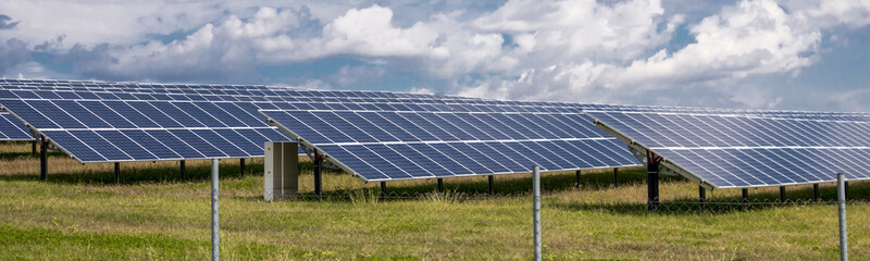 Solar panels on green grass with blue sky