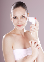 Charming woman with brush for deep cleansing facial. Skin care c