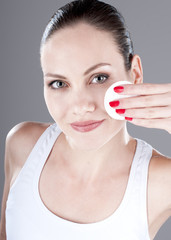 Sensual young woman cleaning skin with  cotton swab, over gray b
