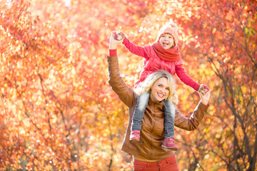 Happy parent and kid walking together outdoor in autumn park. Ye