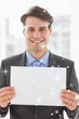 Composite image of happy businessman holding blank page