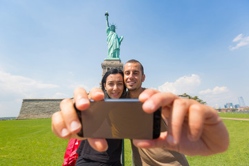 Couple Taking a Selfie with Statue of Liberty on Background