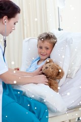 Female doctor listening to a child chest and a teddy bear