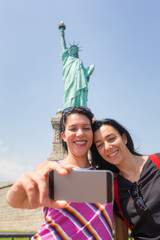 Women Taking a Selfie with Statue of Liberty on Background