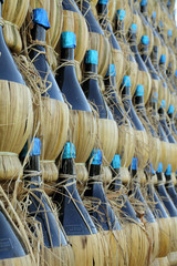 many traditional chianti bottles as background,Tuscany
