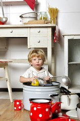 Adorable small child sits in kitchen inside a pan