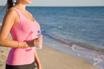 close-up of a fitness young woman with bottle water in hand