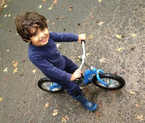 boy riding bike on rainy autum day