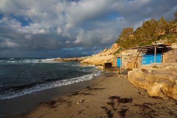 Boat houses on a beach in Milos island, Cyclades, Greece.