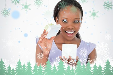 Close up of woman opening a present against a white background