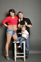 Happy family with pregnant woman on gray background