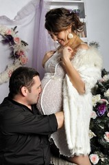 Happy father kisses the pregnant wife on a stomach