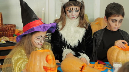 Children In Halloween Costumes Carving