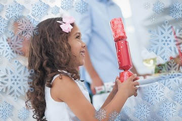 Composite image of cute little girl holding crackers