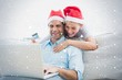 Smiling couple in santa hats shopping online with laptop