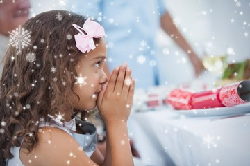 Composite image of little girl sitting praying at table