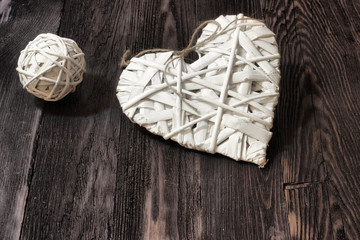 Romantic, white heart and sphere on dark wood