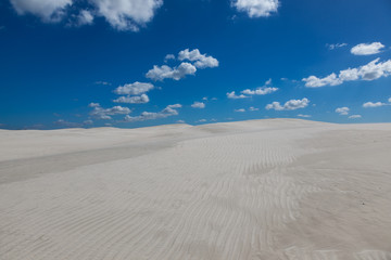 White sand and clouds against a blue sky