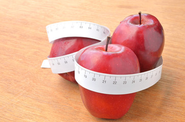 red apple and tape measure on wood background