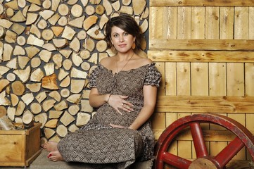 Portrait of a young pregnant woman in rural style