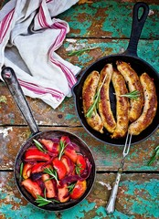 fried sausages with apples, onions and rosemary in a frying pan