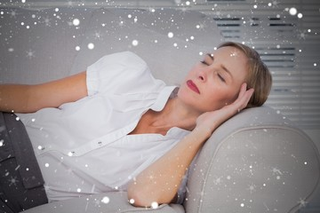 Composite image of businesswoman sleeping on couch