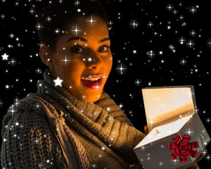Composite image of pretty girl opening a glowing gift