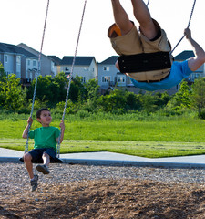 Father and son playing on the swing set at the playground