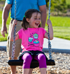 Father and daughter playing on the swing at the park