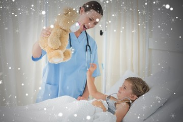 Composite image of doctor entertaining sick girl with teddy bear