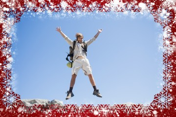 Handsome hiker jumping at the summit smiling at camera