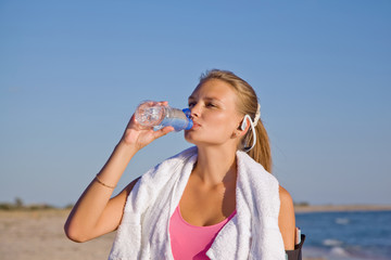 fitness athletic young woman on beach drinking water