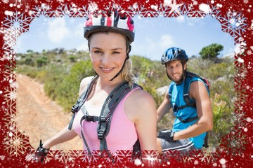 Fit couple cycling up mountain trail smiling at camera